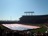 Large USA Flag held across the outfield by a line of dur — Stock Photo