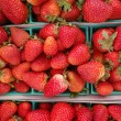 Strawberries displayed in square light blue plastic baskets - Stock Photo