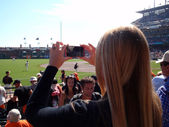 Lady uses Iphone to Photograph baseball game from the crowd — Stock Photo