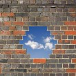 Sky through a hole in a brick wall — Stock Photo