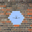 Small plane through a hole in a brick wall — Стоковая фотография
