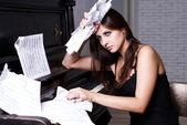 Sad girl near piano — Stock Photo