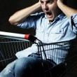 Foto Stock: Guy in shopping cart screaming