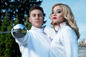 Young couple in fencing costumes — Stock Photo