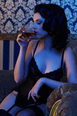Retro girl wearing lingerie with whisky in her hand — Stock Photo