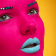 Beautiful girl with pink skin and blue lips on yellow — Stock Photo