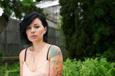 Pretty black haired girl with tattoo in the garden — Stock Photo