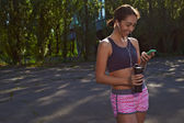 Happy fit girl using phone outdoors — Stock Photo