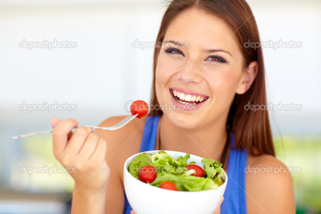 Beautiful young woman enjoying a healthy green salad — Stock Photo #13599266