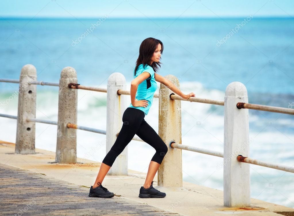 Attractive young woman stretching on the pier at the beach  Stock Photo #13600607