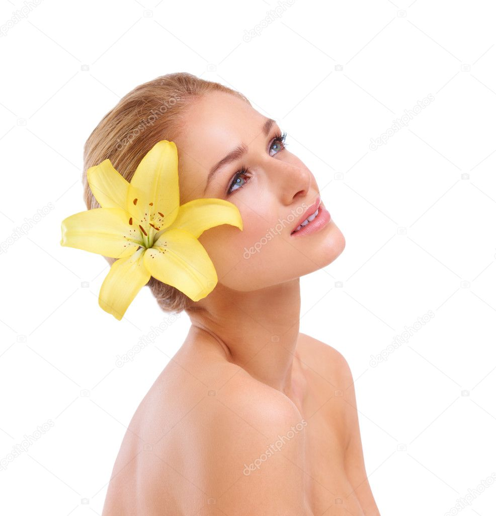 Beautiful young woman with a yellow lily in her hair looking up out of frame — Stock Photo #13602090