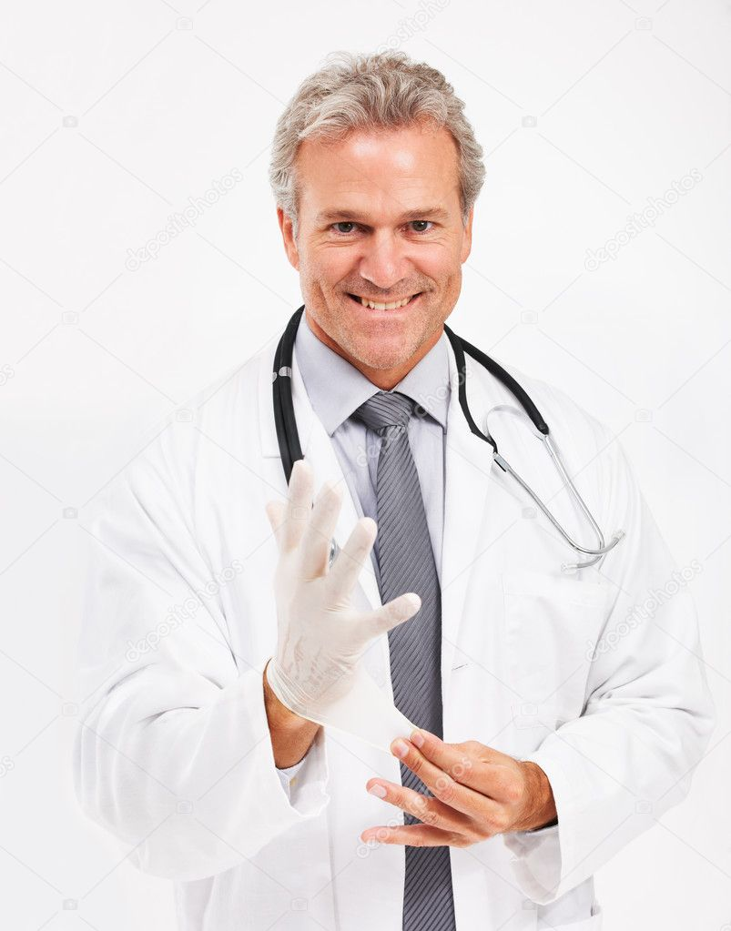 Portrait of a mature medical doctor putting on a surgical glove — Stock Photo #13602962