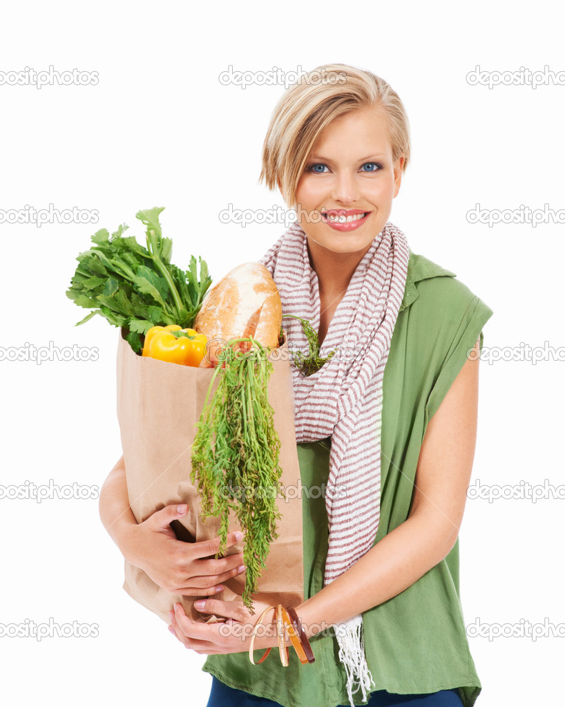 Smiling young woman holding a paper bag of healthy groceries — Stock Photo #13603073