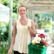Happy young woman smiling at you while carrying a basket of colourful plants in a plant nursery - Stock Photo