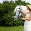 Gorgeous young bride stroking a beautiful white horse - Stock Photo