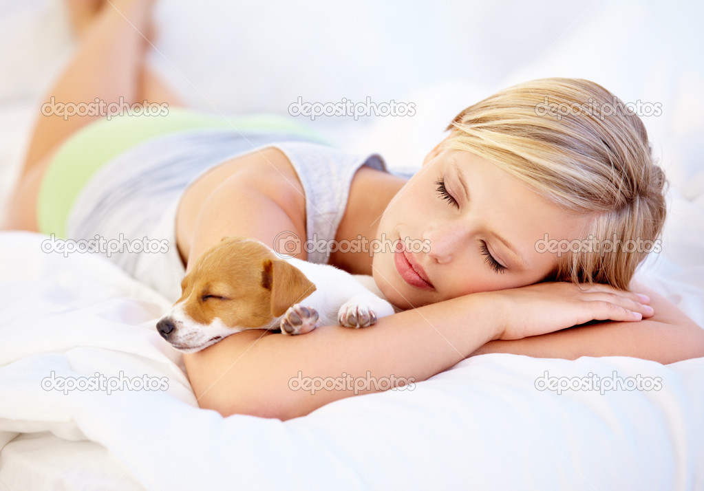 An attractive woman and her cute puppy sleeping on the bed — Stockfoto #17004069