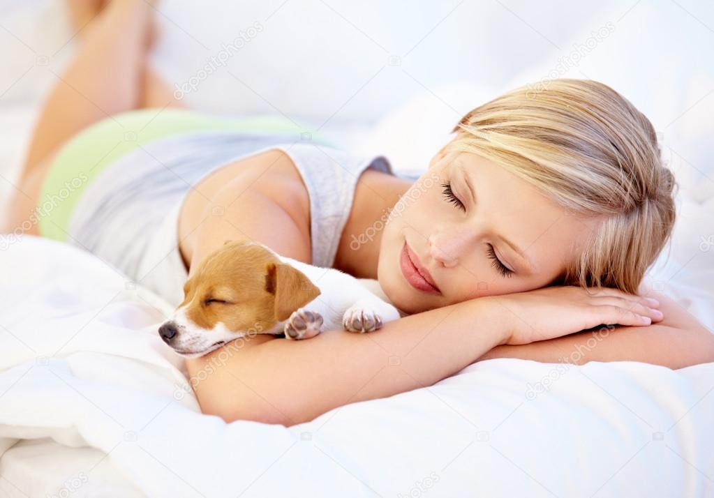 An attractive woman and her cute puppy sleeping on the bed — Stock fotografie #17004069
