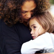 Finding comfort in her mother&#039;s arms - Stock Photo