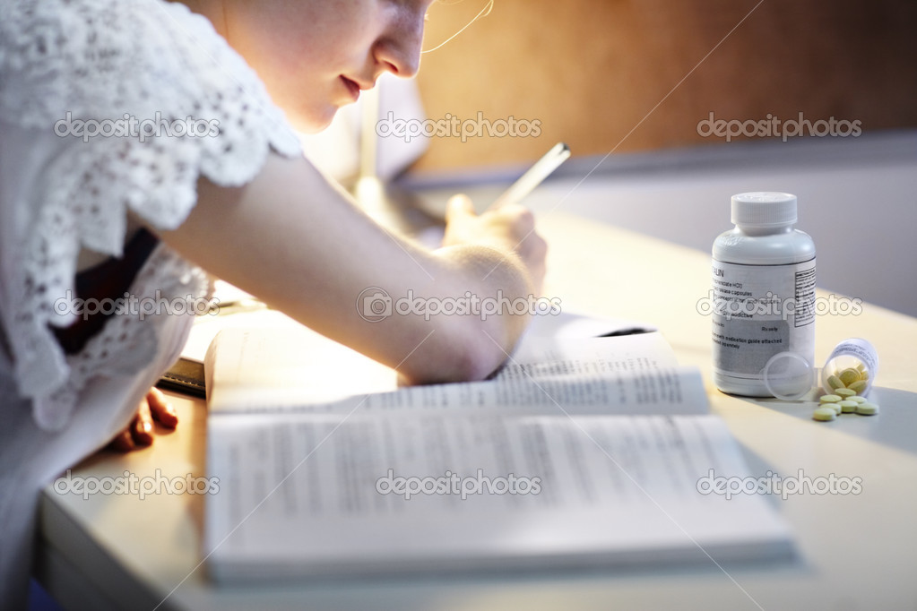 A young woman using medication to help stay awake to study deep into the night — Stock Photo #17148141