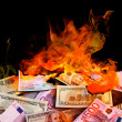 Dollar and euro bills on fire - Stock Photo