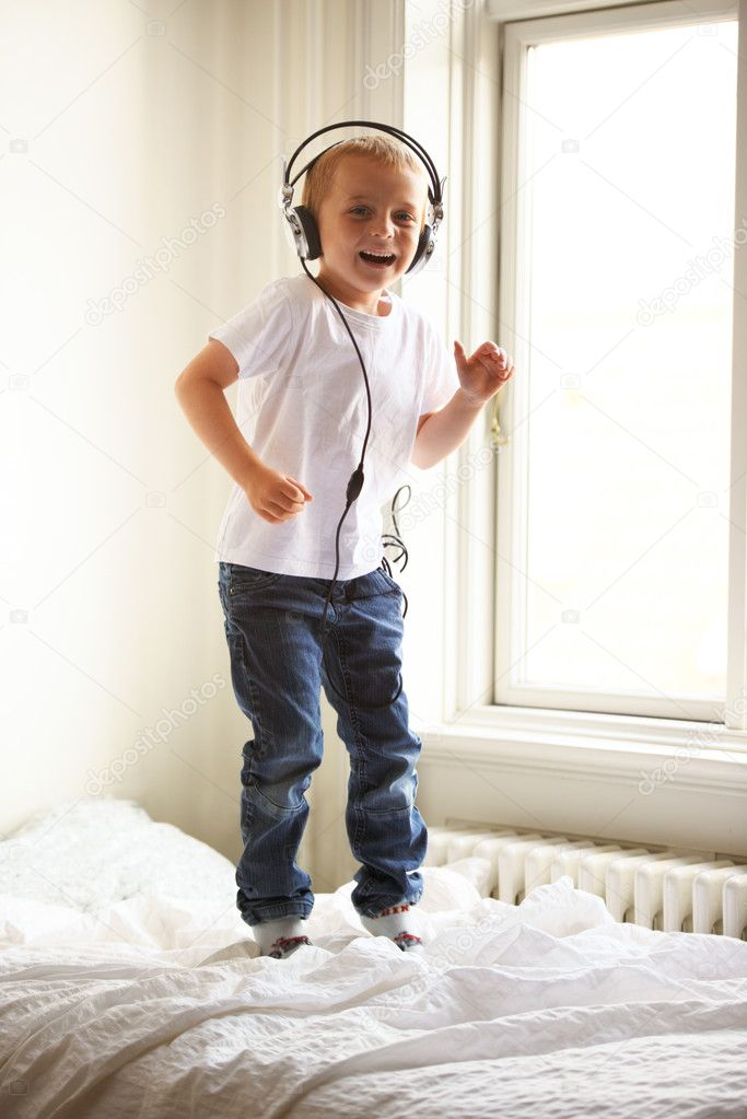 Portrait of a young boy listening to music and jumping on his bed — Stockfoto #17191529