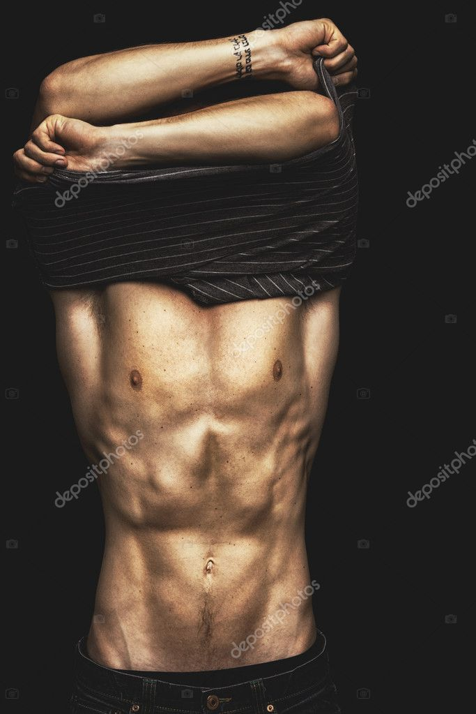 A sexy young man removing his shirt on a black background  Stock Photo #19088981