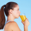 She enjoys a glass of orange juice after exercise - Stock Photo