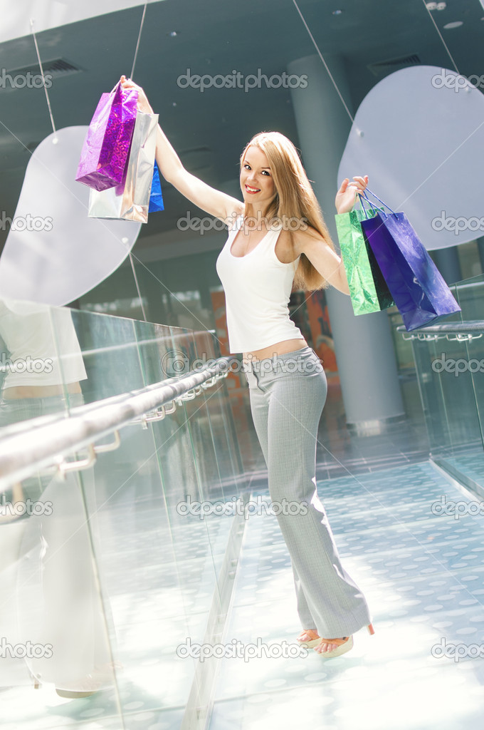 Beautiful woman holding bags in a shopping mall  Stock Photo #12523978