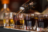 Shots with whisky and liqquor in cocktail bar — Stock Photo