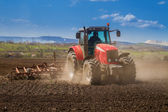 Brand new red tractor working — Stockfoto