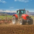 Brand new red tractor plowing the land — Stock Photo #36118815