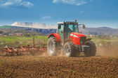 Brand new red tractor plowing the land — Stock Photo