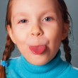 Little girl showing the tongue — Stock Photo #13821479