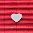 Japanese style love heart on red bamboo mat - Stock Photo