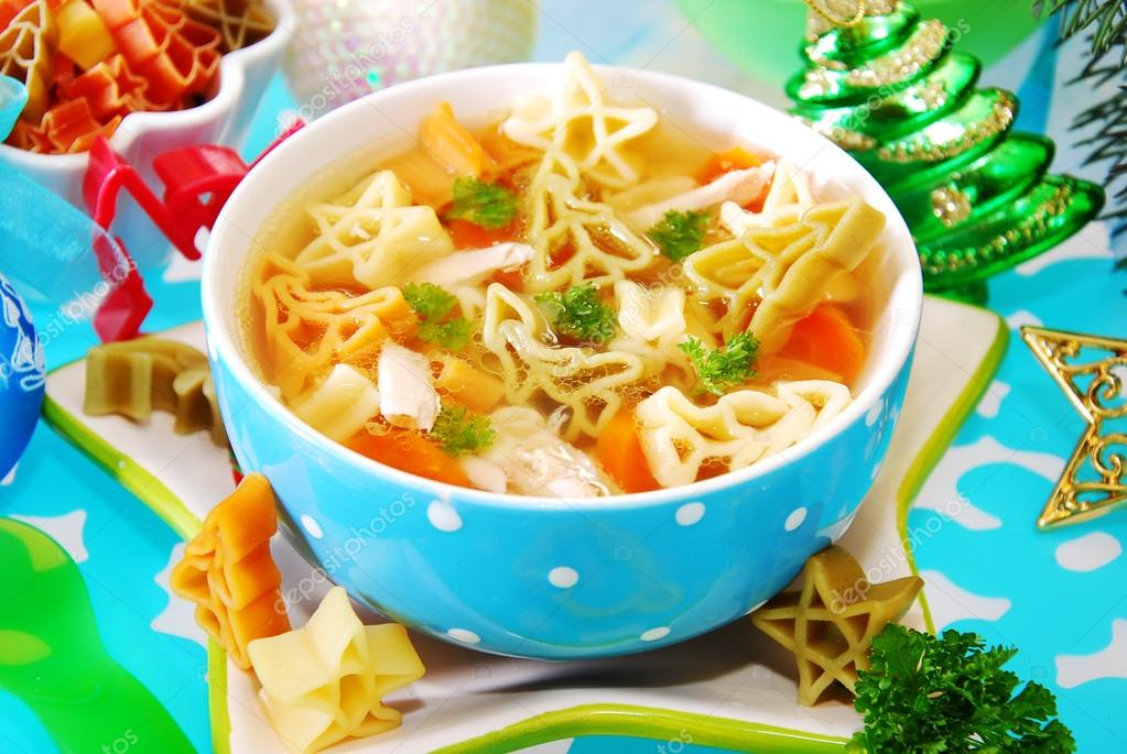 Bowl of chicken soup with christmas symbols shape pasta for child — Stock Photo #13862115