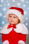 Cute baby in santa hat with snow flakes — Stock Photo