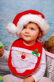 Cute baby in santa hat playing with toys — Stock Photo