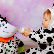 Baby in cow costume feeding a cow mascot - Stock Photo