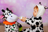 Baby in cow costume feeding a cow mascot — Stock Photo
