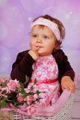 Cute baby girl sitting in white basket — Stock Photo