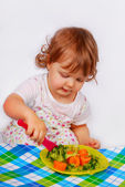 Little baby girl eating broccoli and carrot — Stock Photo