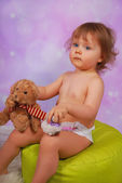 Little baby girl playing with mascots — Stock Photo