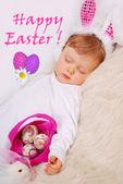 Bebé que duerme en traje de conejito de pascua con saludos — Foto de Stock