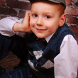 Elegant little boy in a cap and wool vest - Stock Photo