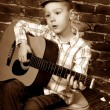 Stock Photo: Little boy playing guitar in vintage style