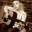 Little boy playing guitar in vintage style — Stock Photo