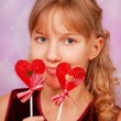 Young girl with two heart shape lollipops — Stock Photo