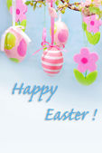 Easter greetings with hanging eggs and felt flowers — Stock Photo
