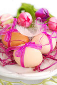 Easter eggs with pink ribbon on the plate — Stock Photo