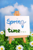 """spring time "" written on easel standing on the grass — Stock Photo"